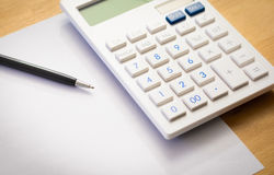 White paper sheet with calculator and pen. On a wood table Stock Image