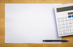 White paper sheet with calculator and pen. On a wood table Royalty Free Stock Photo