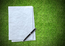 White paper sheet on green grass background Stock Image