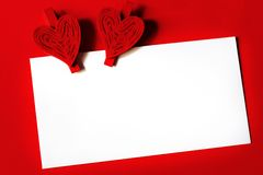 White paper sheet with two hearts on red background Stock Photo