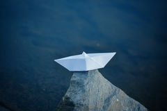 White paper ship sailing on blue water surface. Stock Image