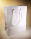 White shopping bag. White paper shopping bag on brown background, studio shot Stock Images