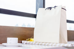 White paper shopping bag and gift placed on table near the windo Royalty Free Stock Photo