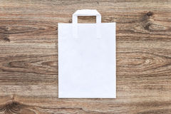 White paper shopping bag on the wooden background. Royalty Free Stock Image