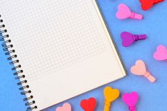 White paper and colored hearts on a blue background. Concept notes for Valentine`s Day royalty free stock photos