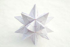 White paper star on snow. White paper star with snow as background stock images