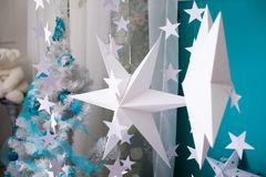 White paper stars on blue background. New Year`s interior. Christmas decorations stock photography