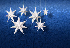 White paper stars on blue brocade royalty free stock images
