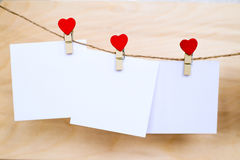 White paper stickers hanging on heart shape pins and pack-thread. White empty paper stickers hanging on red heart shape wooden pins and pack-thread at wooden royalty free stock image