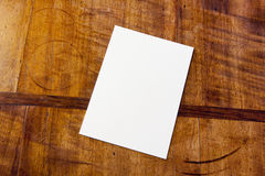White paper on table. White paper pad on antique or aged wooden table stock photo