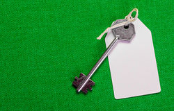White paper tag attached to the metal  silver key on the green b Stock Image