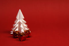 White paper tree and three little gifts on red background Royalty Free Stock Photos