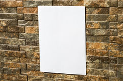White paper on wall. White paper on a rock wall, in sunshine, ideal for poster mock up Royalty Free Stock Photography