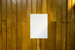 White paper in a wall. White paper in a wood wall, in sunshine, ideal for poster mock up Stock Image