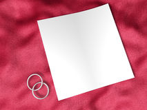 White paper and wedding ring. S on red silk textile Royalty Free Stock Images