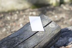 White paper on wood. White paper on a piece of wood, in sunshine, ideal for poster mock up Stock Photos