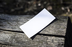 White paper on wood. White paper on a piece of wood, in sunshine, ideal for poster mock up Stock Photography