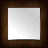 White paper on a wooden wall. Stock Photography