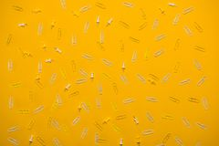 White paperclips and pins. Composition of white paperclips and pins on yellow Royalty Free Stock Images