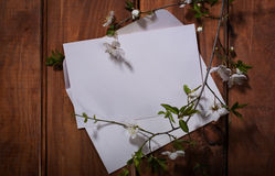 White papers with flower on wooden background Royalty Free Stock Photography