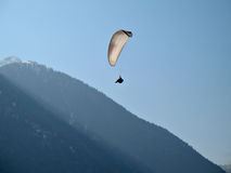 White Paraglide. A paraglider is flying in the blue sky near a mountain with his paraglide Stock Photos