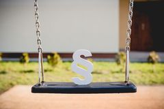 White paragraph symbol on children chain swing. Family law or playground accident concept stock images