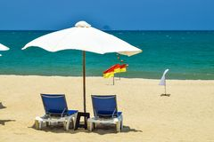 White parasol with two chairs on beach near sea on sunny day stock photography