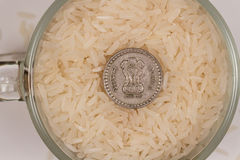 White parboiled rice in a glass mug and five Indian rupees. Rice poured almost to the edge of the cup, coins lies above. Photo is ideal for website design or Stock Photos