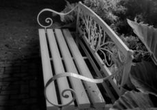 A Park Bench Awaits a Stranger. A white park bench in contrast to a black and white background is a strong image. Sit down and have a rest . The lovely ornate royalty free stock photos
