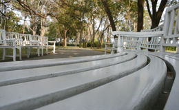 White park benches in blurred. Long curved row of white park benches in blurred Stock Images