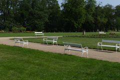 White park benches. With green grass Royalty Free Stock Image