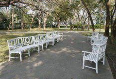 White park benches. Long curved row of white park benches Royalty Free Stock Photos