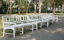 White park benches. Long curved row of white park benches Stock Image