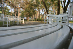 White park benches. Long curved row of white park benches in blurred Stock Images