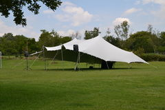 White party tent. Event or party tent on geen grass field with trees in background Royalty Free Stock Photo