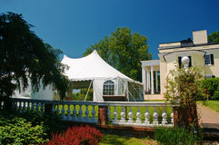 White party tent at mansion. Large white party tent set up on a front lawn of a large mansion for a wedding Stock Image