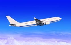 White passenger aircraft in blue sky Stock Photos