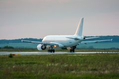 White passenger airplane taxiing to the runway. White passenger aircraft taxiing to the runway stock images