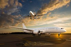 White passenger airplane on airport runway. White passenger airplane on airport runway during sunset. And aircraft climb in the sky Royalty Free Stock Images