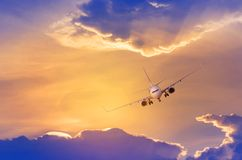 White passenger airplane flying away in to sky high altitude with iridescence cloud or rainbow cloud. During sunset Royalty Free Stock Images