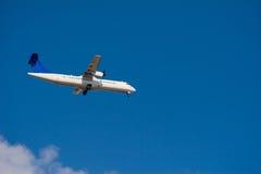 White passenger Airplane flying in blue sky Stock Photos