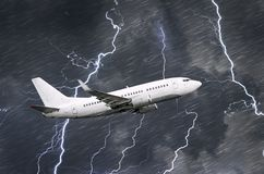 White passenger airplane takes off during a thunderstorm night lightning strike of rain, bad weather. Stock Photography
