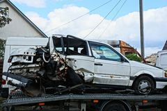 White passenger car crashed in an accident stands on a tow truck royalty free stock photo