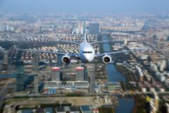 White passenger plane in flight. White passenger plane flyes above the buildings, city quarters and river. Front view of aircraft Stock Photography