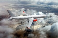 White passenger plane in flight. The plane flies against a background of clouds and mountain landscape Stock Images