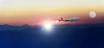 White passenger plane flying in the blue sky above the mountains Royalty Free Stock Photos