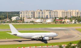 The white passenger plane is moving along the taxiway and getting ready to take off Stock Photography
