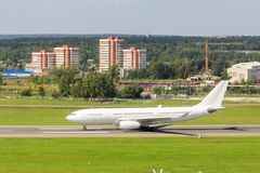 The white passenger plane is moving along the taxiway and getting ready to take off Royalty Free Stock Photography