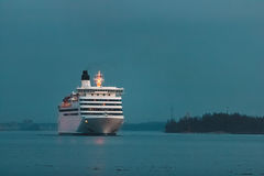 White cruise liner. White passenger ship sailing in evening in still water Stock Image