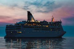 White cruise liner. White passenger ship sailing in evening in still water Stock Photo